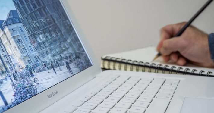 image of person writing on notepad about finance broker